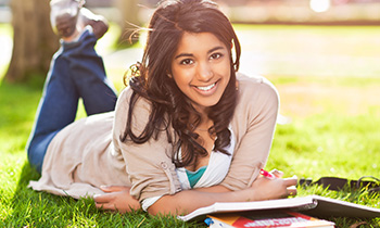 Young woman laying in the grass with study materials.